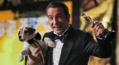 "Best actor winner Dujardin of France carries Uggie the dog after ""The Artist"" wins the Oscar for Best Picture at the 84th Academy Awards in Hollywood"